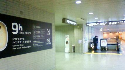 ナインアワーズ成田空港への案内表示とエスカレーター